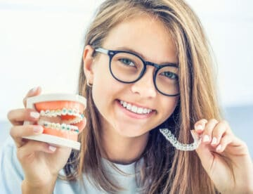 Dental invisible braces or silicone trainer in the hands of a young smiling girl. Orthodontic concept